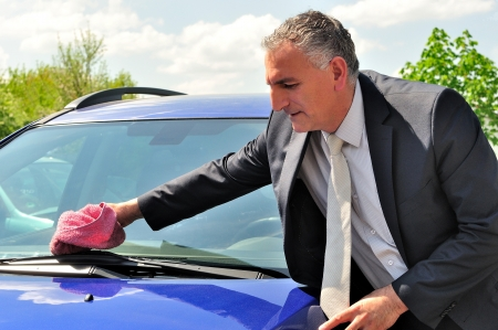 Man wearing suit cleaning blue car at lunch brake  photo