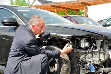 accidental: Man in suit inspecting car damage