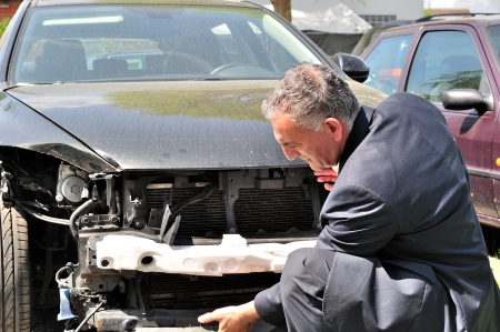accident damage: Man in suit inspecting car damage