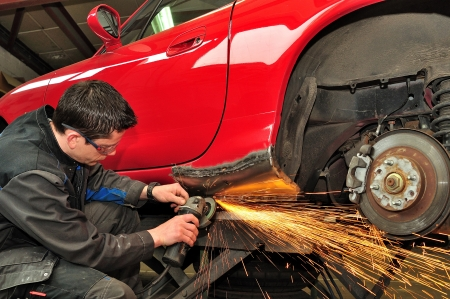 auto garage: Worker repairing car body