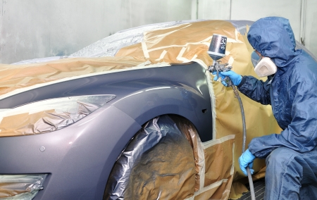 Worker painting car in a paint booth