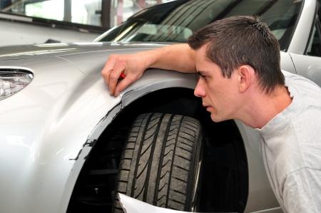 expert: Car insurance expert, inspecting car damage. Stock Photo