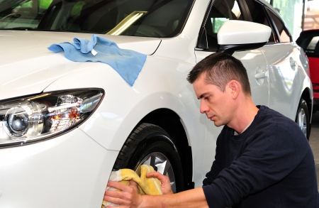 car cleaning: Man cleaning a whie car  Stock Photo