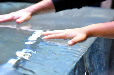Hand of a child boy on melting ice  photo