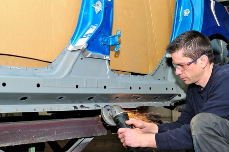 Proffesional worker grinding car body