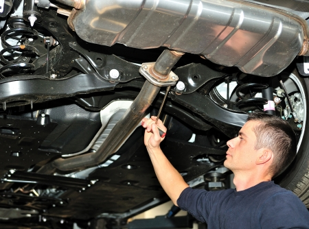car exhaust: Car mechanic working on exhaust