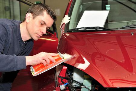 Mechanic repairs a red bonnet