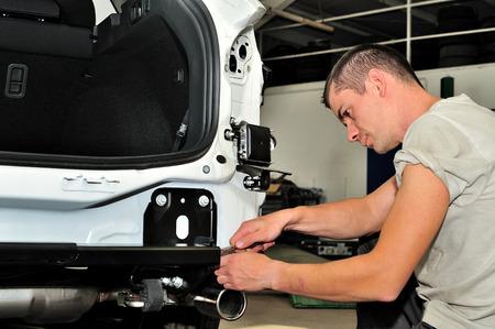 Mechanic assembling trailer hitch