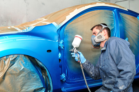 painter: Painter working with blue car  Stock Photo