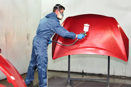 bodywork: Professional car painter, painting red bonnet  Stock Photo