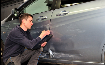 appraise: Man inspecting car damage after an accident  Stock Photo