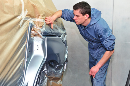 Man inspecting newly painted car