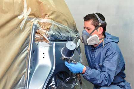 Worker painting silver car in a paint box