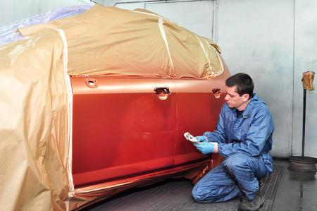 Professional car painter checkichg his work  photo