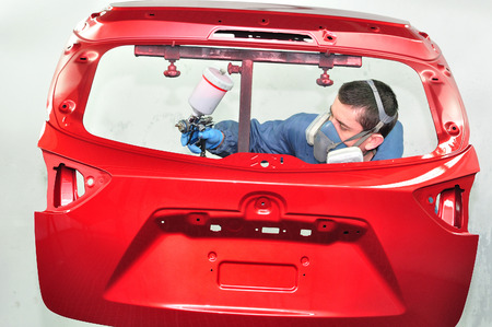 car body: Spraying rear door in red base coat.