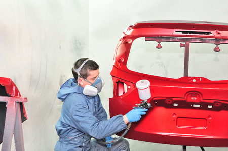 Worker painting red car part. Stock Photo