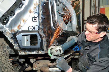 welds: Proffesional car body repair, grinding welds. Stock Photo