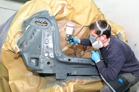 Worker spraying gray base coat. photo