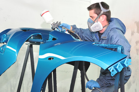 Painting blue car bumper by proffesional. photo