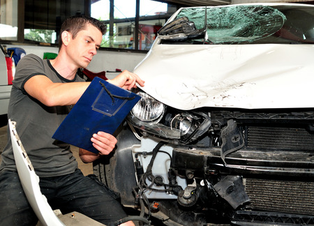 insurance themes: Insurance agent inspecting car damage. Stock Photo