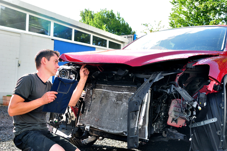 insurance themes: Inspecting car damege after crash.