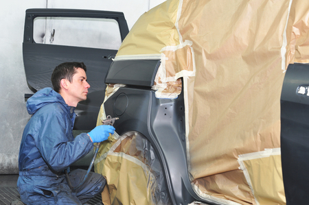 car body: Proffesional car body repair, Painting side panel. Stock Photo