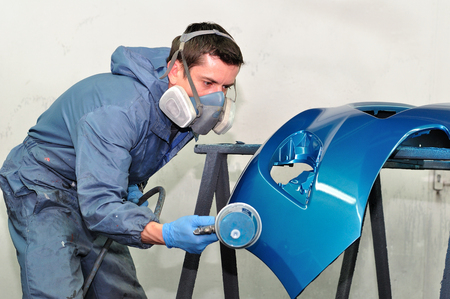 Proffesional car body repair, Painting blue bumper. Archivio Fotografico
