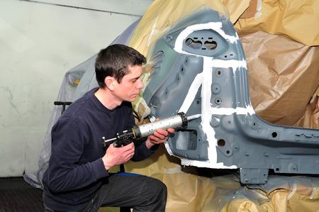 sealing: Worker sealing panels with caulk.