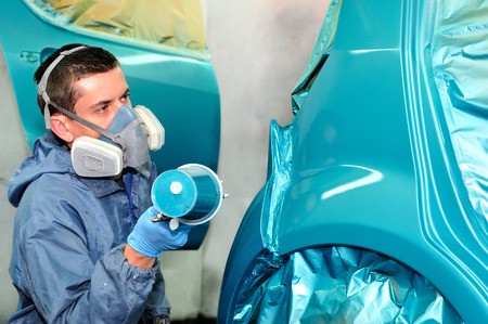 body shop: Worker painting blue car in body shop.