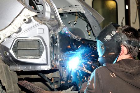 welding mask: Body shop worker welding car panel.