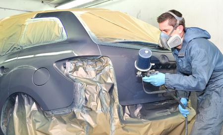 hombre pintando: Pintura de vehículos profesional después de la reparación del cuerpo.