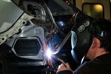 car body: Body shop worker welding car panel.
