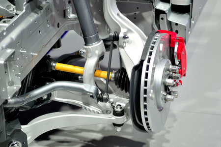 brake caliper: Car disc brake with red caliper, and  front suspension.