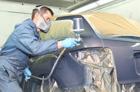 priming paint: Worker painting a gray car in a paint chamber. Stock Photo