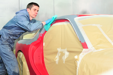 car body: Body worker preparing car surface for paint.