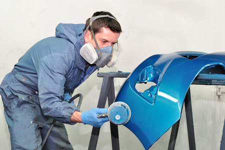 body painting: Professional painting of blue car bumper. Stock Photo