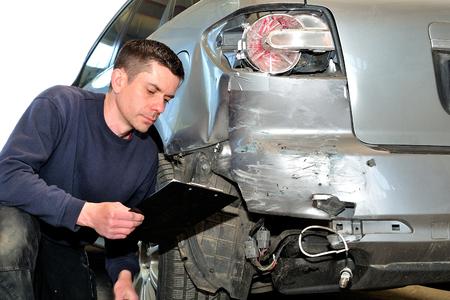 mecânico de seguros no trabalho na oficina de carro. Foto de archivo