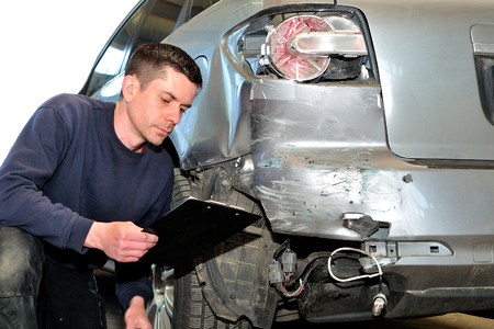 verzekering monteur aan het werk in de carrosseriebouw. Stockfoto