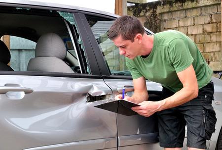 bulge: insurance mechanic at work in car body shop.