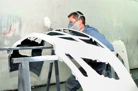 Professional body shop worker painting white car bumper. Stock Photo