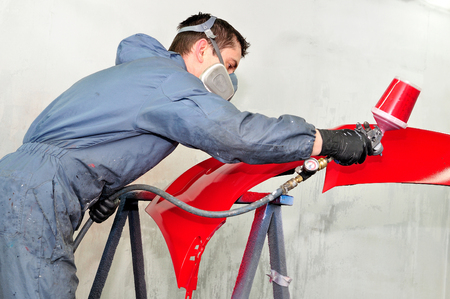 Professional body shop worker painting red ca bumper. Stock Photo