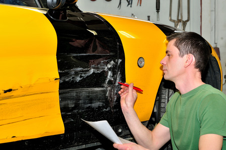 Professional body shop worker painting black car. Imagens