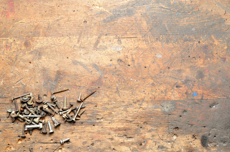 Old used dirty workbench with screws for background.