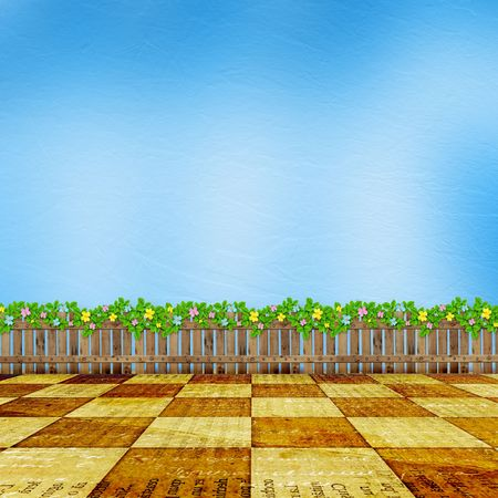 Wooden fence with a flower garland on the background of a summer day photo