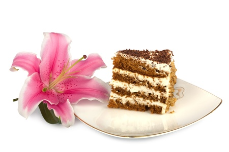 Piece of cake on a plate and a beautiful pink lily photo