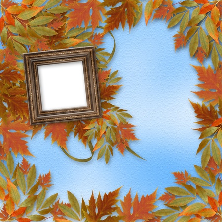Bright autumn leaves on the abstract background with wooden frame photo