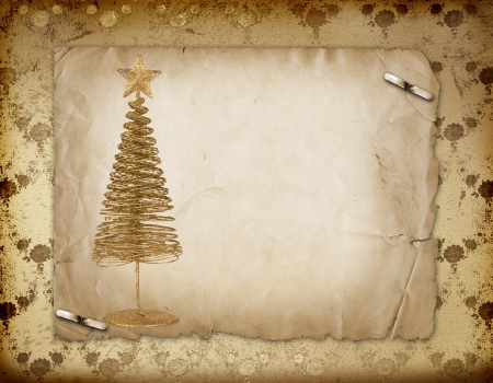 Christmas greeting card with gold metal firtree on the paper floral background photo