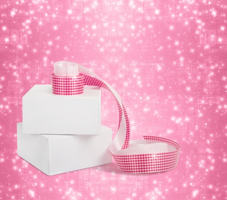 White boxes with gifts with pink ribbons on the beautiful abstract background photo