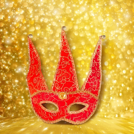 Carnival red mask on  gold abstract background with bokeh effect photo