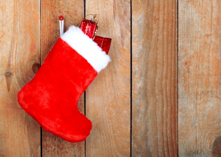 stockings: Red christmas boot with gifts on background wooden wall